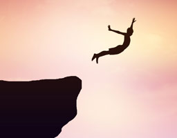 person leaping off rock - silhouette